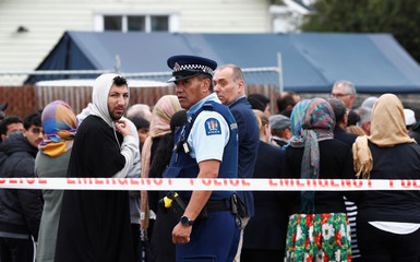 Police stand guard as members of Muslim religious groups gather for prayers outside the Linwood Mosque in Christchurch