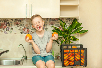 Portrait of a boy with blond hair who holds oranges and laughs in the kitchen. The concept of children's health and proper nutrition. Vitamins for children