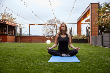 one young lady, 20-29 years old, meditating in a backyard of a fancy house with a beautiful view on mountains. sitting on yoga matt.