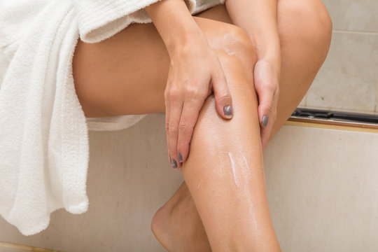Closeup photo of young woman body care cream on legs after having bath