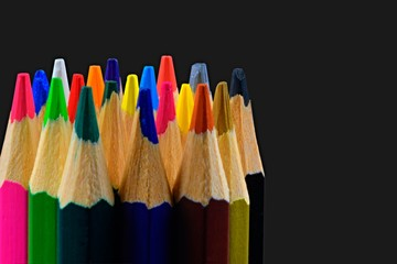 Close up of an assortment of colored pencils tips on black background. Background of colorful pencils. Creative idea and concept. Drawing and painting. School and education. Art. Copy space. Free