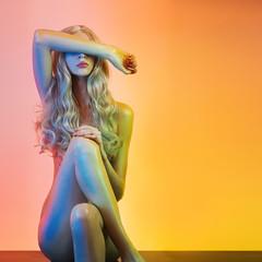Beautiful slim woman posing in colorful light.