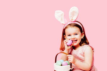 Portrait of a happy little toddler girl with easter bunny ears and a basket of eggs
