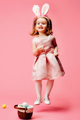 Portrait of a jumping toddler girl with easter bunny ears isolated on pink