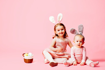 Portrait of a little toddler girl and a baby with bunny ears and easter eggs basket, on pink