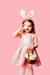 Happy Easter! Portrait of a little toddler girl holding a basket of easter eggs  and one egg covering her eye
