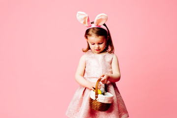 Portrait of a little toddler girl with easter bunny ears and basket of easter eggs, isolated on pink