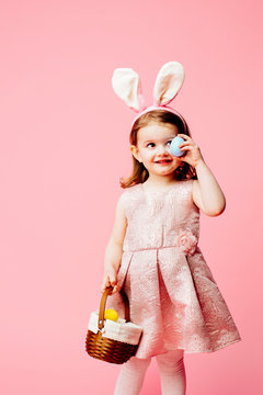 Portrait of a little toddler girl with bunny ears and easter egg