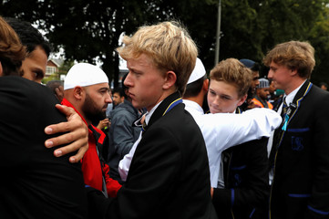 High school students embrace as they give hugs to Muslims waiting for news of their relatives at a community centre, following Friday's shooting in Christchurch