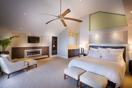 Bedroom with white king size bed and big ceiling fan.