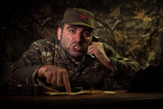 The evil dictator sitting on table. Angry communist general sitting at headquarter or Cuban commander in dark room.