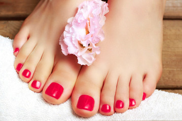 La pose en embrasure Pedicure Pink pedicure with flower close-up, isolated on a wooden background, top view