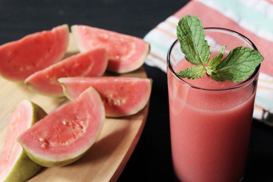 Glass of guava smoothie and slice of its fruit