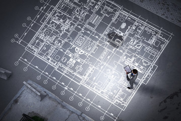 Man engineer thinking over his plan. Mixed media