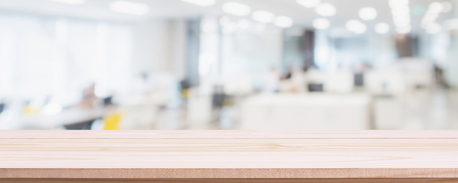 Empty wood table top and blur glass window wall in office building background - can used for display or montage your products.