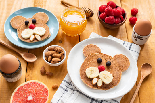 Pancakes breakfast for kids, food art. Bear or Walrus shape pancake decorated with fruit, berries and nuts on wooden table. Children meal