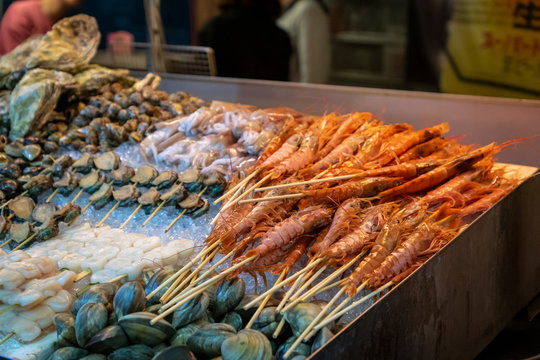 shrimps, oysters, scallops, shellfish and fresh seafood in street food stall in Asian night market