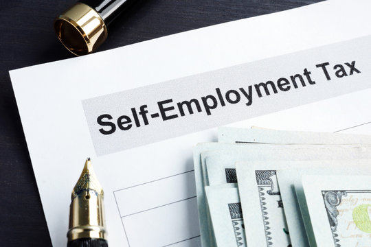 Self employment tax form and money with calculator.