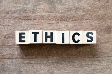 Letter block in word ethics on wood background