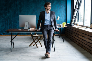 Businessman wearing modern suit and stands in contemporary office.