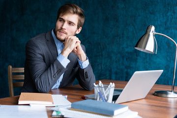 Shot of young man sitting at table looking away and thinking. Thoughtful businessman sitting in office.