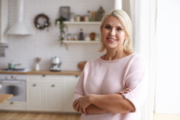 Attractive middle aged housewife with blonde hair and brown eyes posing indoors in her modern clean stylish kitchen interior, crossing arms on her chest and looking at camera with pleased smile