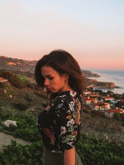 Brunette girl with long hair, in a skirt and a shirt with a print stands at sunset, behind the house of the coast of Los Angeles, the ocean and the beautiful sky
