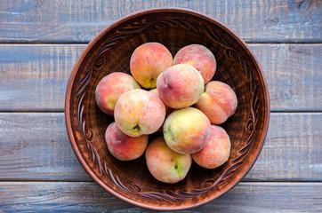 Ripe peaches in a clay dish.