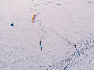 Male athlete on mountain skiing with dreams kite free ride on frozen lake. Aerial view. Snowkiting