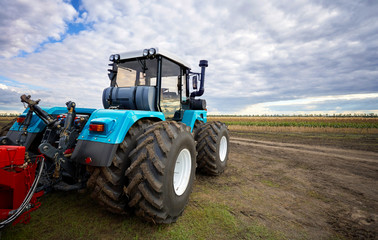 Fototapete - Tractor working in a field against a cloudy sky