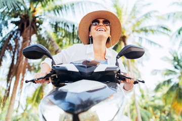 Happy smiling woman in straw hat and sunglasses riding motorbike under palm tree