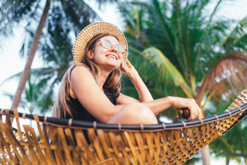 Happy smiling young woman in straw hat in sunglasses sitting in hammok and enjoy morning sun light