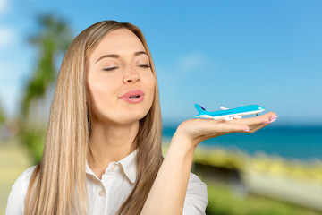 Travel air plane concept.Young smiling woman holding hand model air plane.