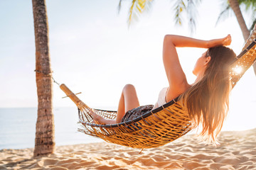 Young beautiful longhaired woman relax in hammok on the sand beach