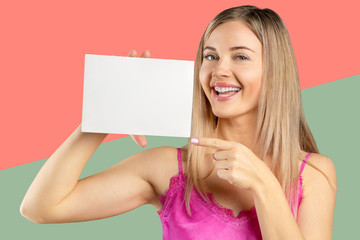 Happy smiling beautiful young woman in pink smart casual clothing showing blank signboard or copyspace for slogan or text