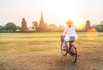 Woman riding bicykle near Ayutthaya historical park in Thailand, early morning time
