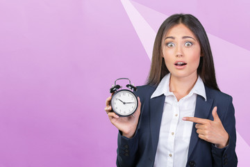 young woman holding a clock. time management concept.