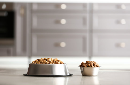 Bowls with dry pet food on floor