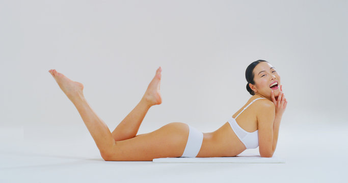 Portrait of young asian  woman with perfect body lying on the floor and showing her hairless soft and silky legs after depilation isolated on a white background.