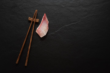 Space wood chopstick with fish slice on black marble background