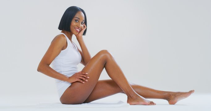 Portrait of young dark skin woman with perfect body touching gently her hairless soft and silky legs after depilation isolated on a white background.