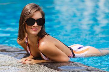 Beautiful slim brunette in sunglasses on vacation