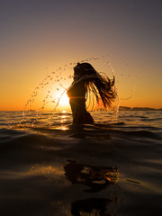 Woman in the sea at sunset flipping her hair out of the water