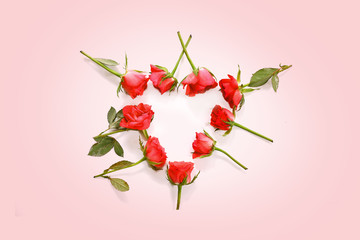 red roses laid in a heart shape on a light pink background, love concept with copy space