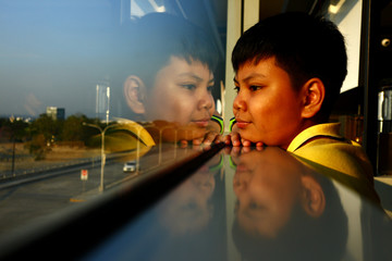 Young Asian boy looking out a glass window