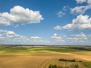 Panoramic landscape with endless farmlands and white big clouds in a blue sky in a summer day. Aerial view from drone.