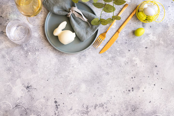 Beautiful Easter table setting in Scandinavian style. Green mint plate with bunny, painted  egg and  cold cutlery on modern concrete background decorated with plant. Copy space.Top view