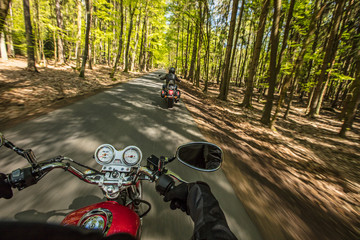 Motorcycle driver riding in spring forest, handlebars view.
