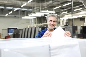 Obraz Drukarnia. Papier do  druku. Drukarz wybiera  odpowiednią gramaturę papieru mierząc go miernikiem. - fototapety do salonu