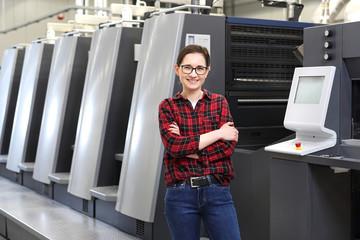 Obraz Praca w drukarni. Uśmiechnięta kobieta, pracownik drukarni stoi w hali produkcyjnej na tle nowoczesnych maszyn drukarskich - fototapety do salonu